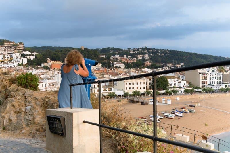 España, Tossa de Mar, agosto de 2018 Una muchacha examina la ciudad a través de un telescopio fotografía de archivo libre de regalías