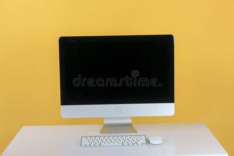 espa?o de trabalho com o computador na casa ou no est?dio, amarelo da parede do fundo fotografia de stock royalty free