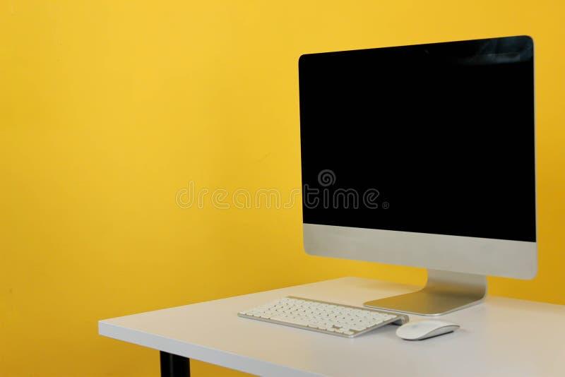 espa?o de trabalho com o computador na casa ou no est?dio, amarelo da parede do fundo fotografia de stock