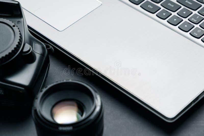 Espa?o de trabalho na tabela preta do fot?grafo Espa?o de trabalho m?nimo com port?til, c?mera e lente imagens de stock