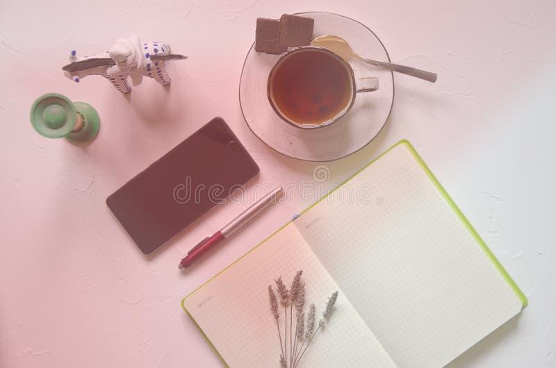 Espace de travail avec le bloc-notes, tasse de th? sur un fond blanc Configuration plate, bureau de bureau de vue sup?rieure Ind? photos stock