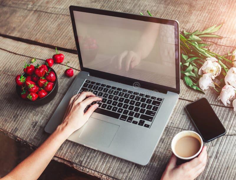 Espace de travail avec les mains de la fille, ordinateur portable, bouquet des fleurs de pivoines, café, fraises image libre de droits