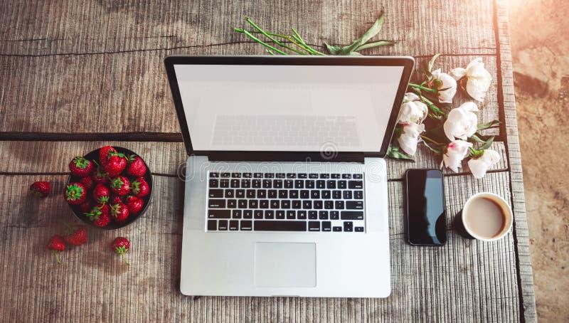 Espace de travail avec les mains de la fille, ordinateur portable, bouquet des fleurs de pivoines, café, fraises images libres de droits