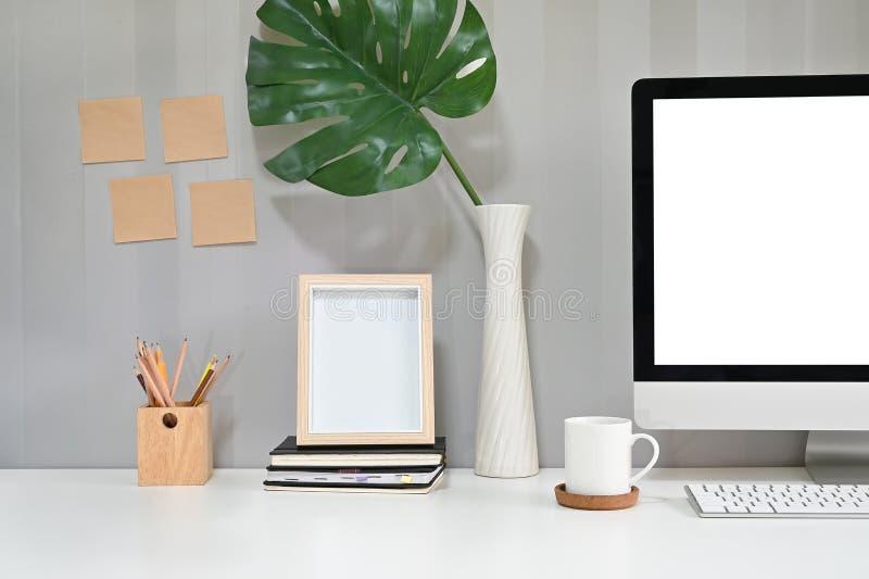 Espace de travail avec ordinateur, tasse de café, crayon et cadre photo avec note collante sur le mur photo stock