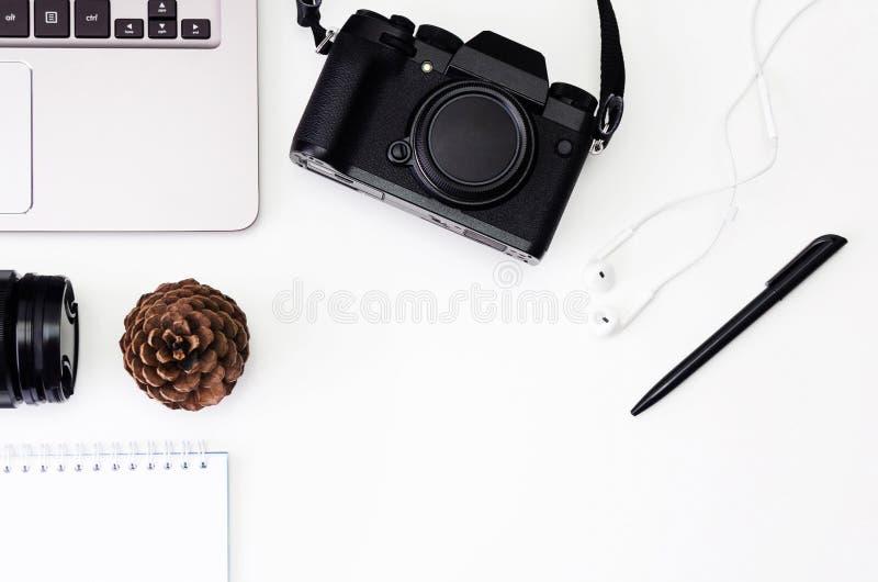 Espace de travail de bureau de vue supérieure avec le clavier d'ordinateur portable, appareil-photo de hippie, lentille, bloc-not image libre de droits