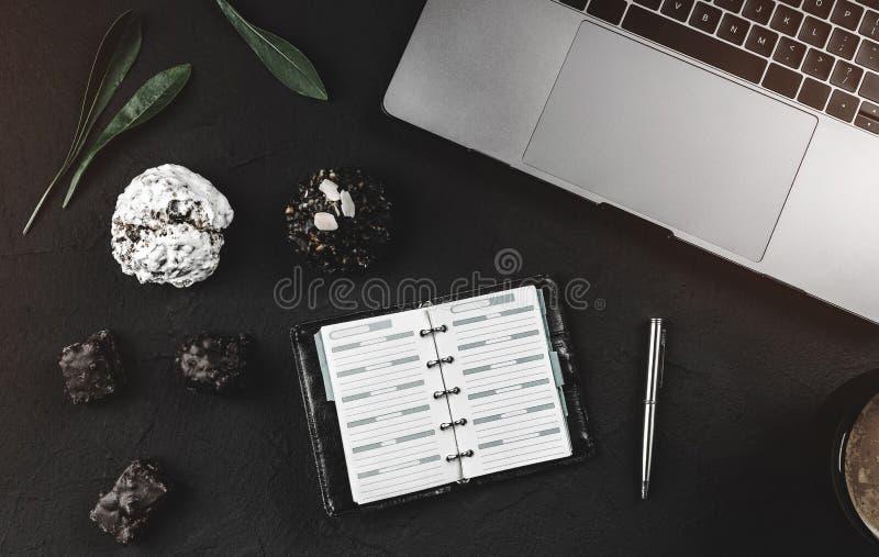 Espace de travail moderne pour un homme d'affaires, ordinateur portable et bloc-notes de travail, bonbons avec du chocolat et caf images libres de droits