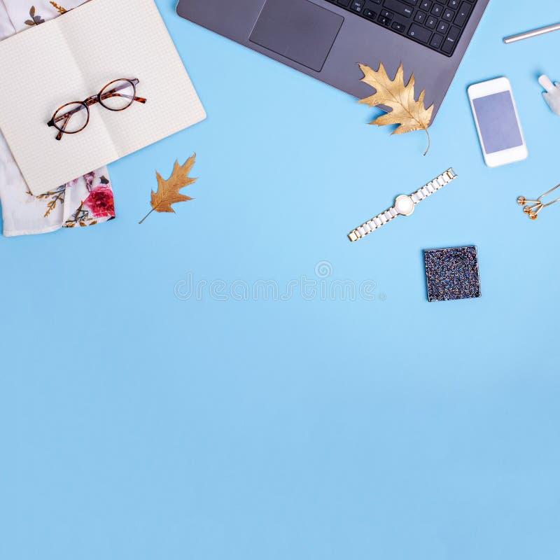 Espace de travail de siège social avec l'ordinateur portable, les verres et la robe sur le fond bleu Concept de travail de blogge photographie stock