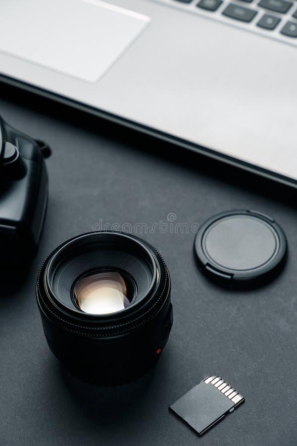 Espace de travail sur la table noire du photographe Espace de travail minimal avec l'ordinateur portable photos stock