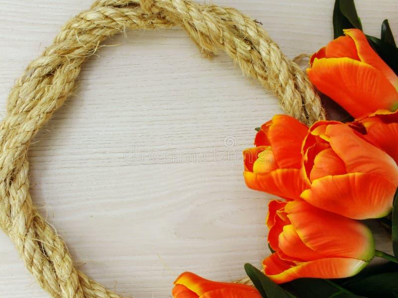Espace o fundo com beira artificial do ramalhete das flores da tulipa e da corda do cânhamo imagem de stock