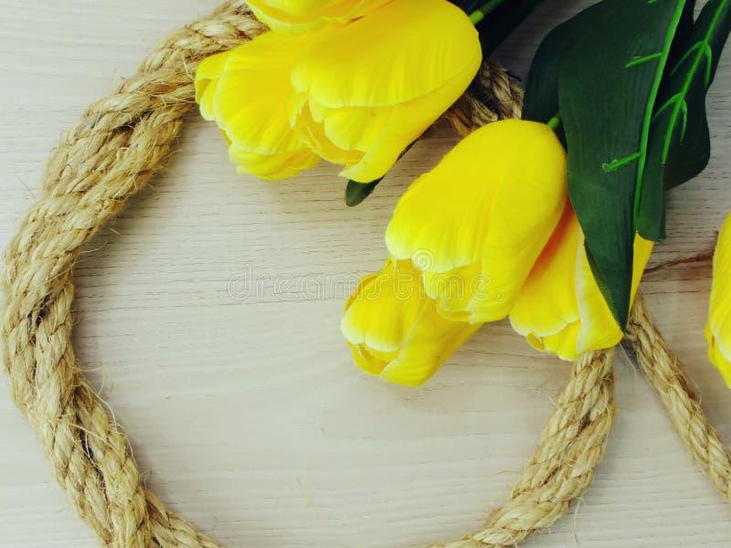 Espace o fundo com beira artificial do ramalhete das flores da tulipa e da corda do cânhamo imagem de stock royalty free