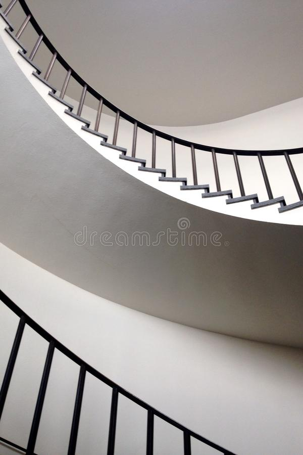 Espace vital minimaliste avec l'escalier en spirale photographie stock libre de droits