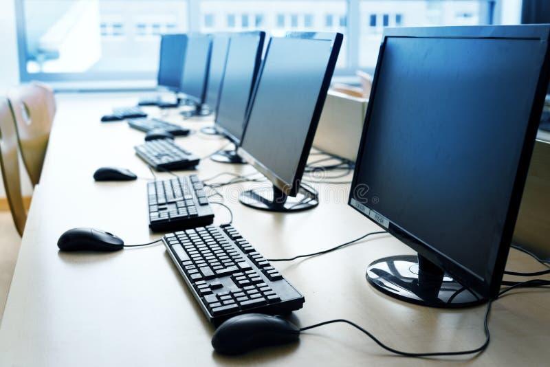 Espaces de travail d'ordinateur de PC dans une rangée pour les travailleurs, le programmeur ou les étudiants créatifs dans un lab photographie stock