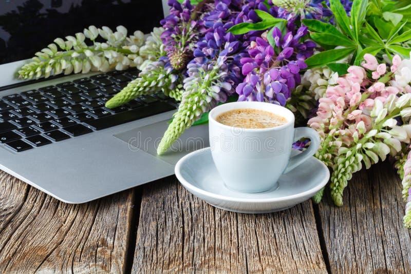 Espacio de funcionamiento o lugar de trabajo con el ordenador portátil, las flores y el café imagenes de archivo