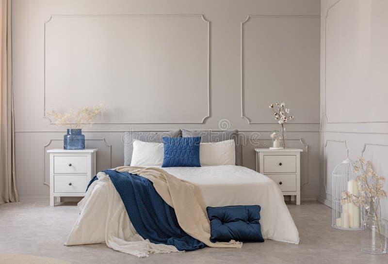 Espacio de la copia en la pared gris del dormitorio escandinavo interior con diseño azul, blanco y gris fotografía de archivo