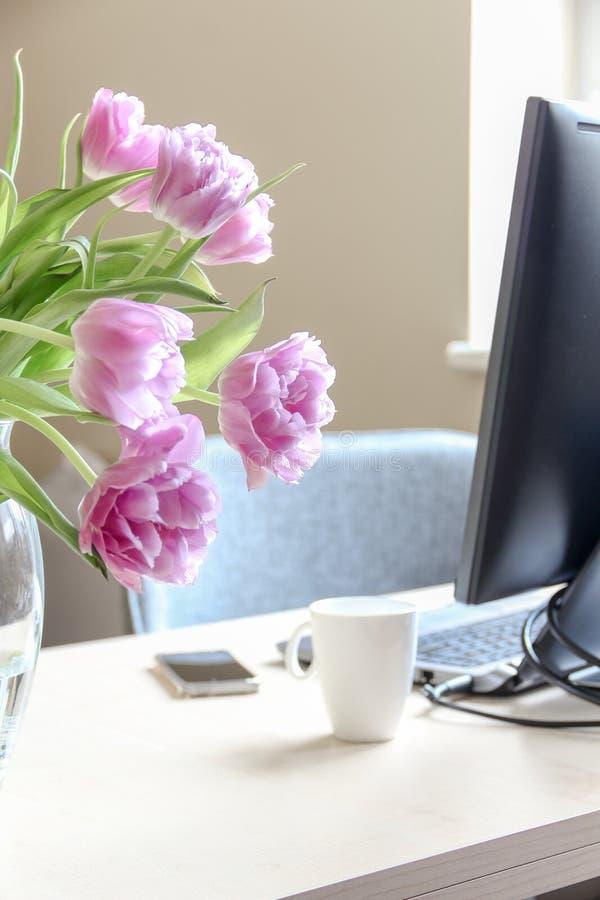 Espacio de trabajo acogedor y un ramo de tulipanes rosados en un florero imagen de archivo