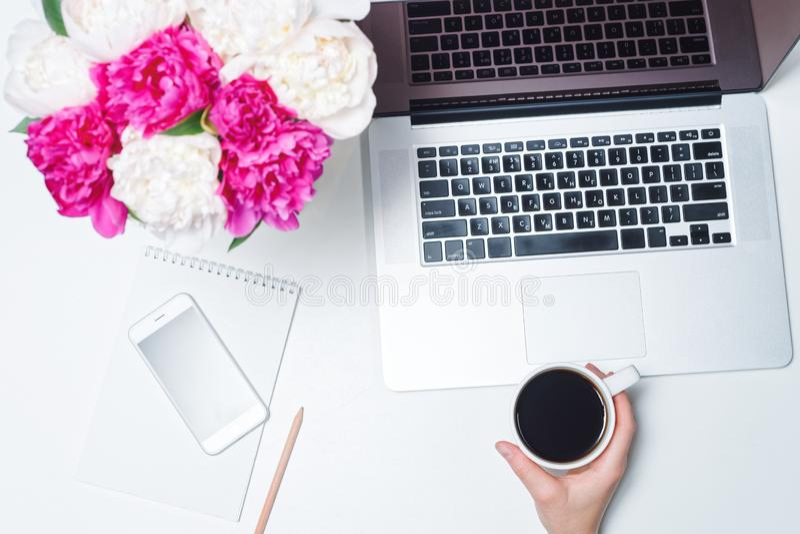 Espacio de trabajo con el ordenador portátil, el teléfono móvil, la taza de café y de mano femenina, el cuaderno, las plumas, y l imagen de archivo libre de regalías