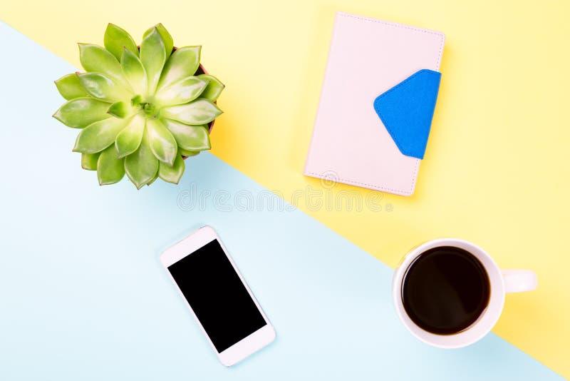 Espacio de trabajo conceptual o concepto del negocio Planta verde en un pote, la taza de café, el cuaderno y el teléfono móvil mo fotografía de archivo