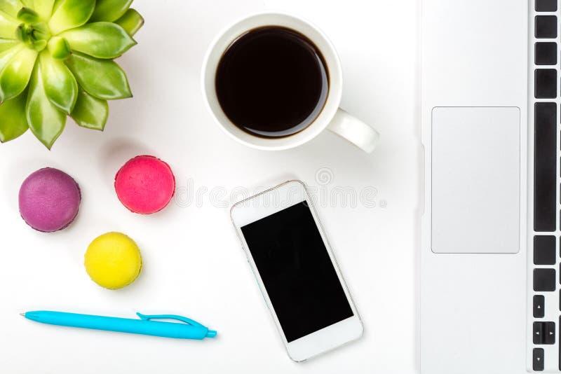 Espacio de trabajo conceptual o concepto del negocio Planta verde en un pote, la taza de café, macarrones coloridos, pluma azul,  fotografía de archivo