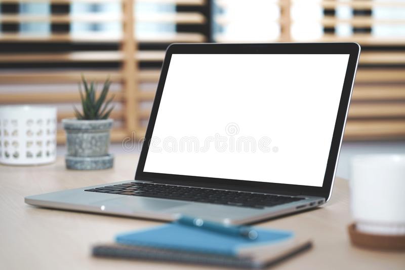 Espacio de trabajo conceptual, ordenador portátil con la pantalla blanca en blanco en la tabla fotografía de archivo libre de regalías