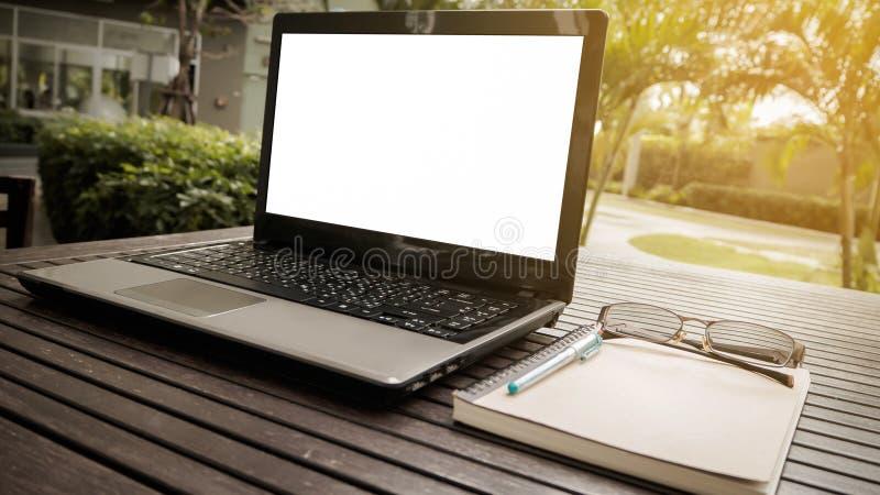 Espacio de trabajo conceptual, ordenador portátil con la pantalla en blanco fotografía de archivo