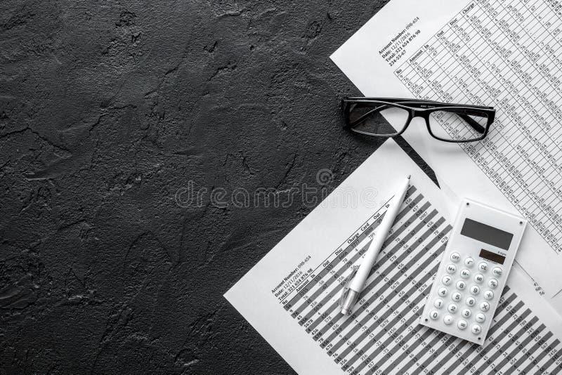 Espacio de trabajo de la contabilidad con la calculadora, el beneficio y las tablas en maqueta de escritorio oscura de la visión imagen de archivo libre de regalías