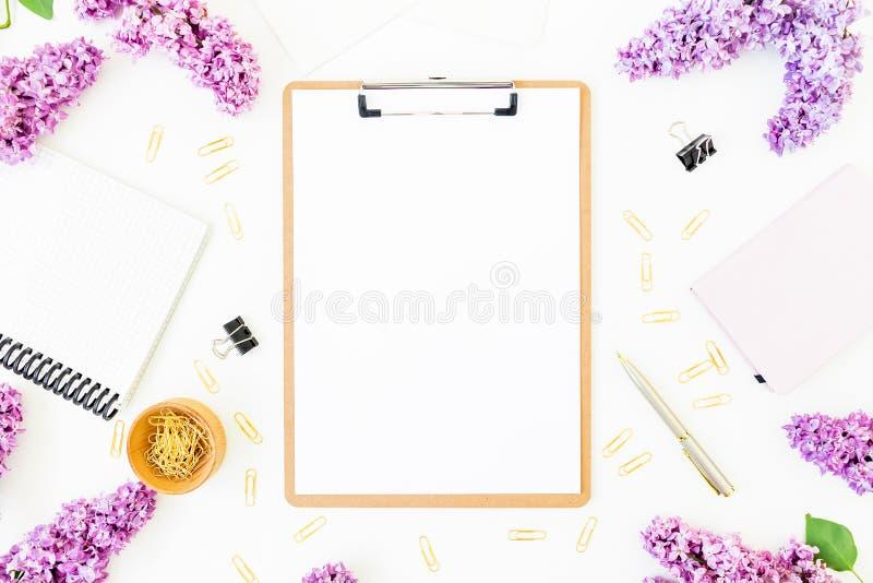 Espacio de trabajo de Minimalistic con el tablero, el cuaderno, la pluma, la lila y los accesorios en el fondo blanco Endecha pla imagen de archivo