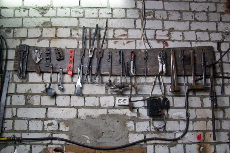 Espacio de trabajo del herrero Algunas herramientas en la pared imagen de archivo libre de regalías
