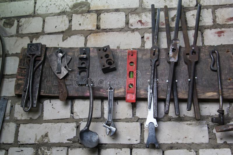 Espacio de trabajo del herrero Algunas herramientas en la pared Ciérrese encima de tiro imagen de archivo libre de regalías