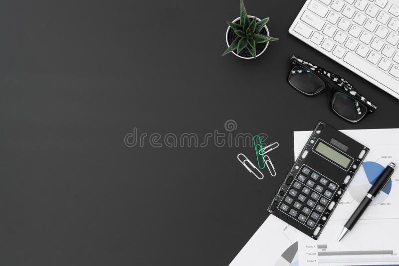 Espacio de trabajo de escritorio puesto plano de la oficina del teclado inalámbrico, gráfico y cartas del informe, pluma, calcula foto de archivo