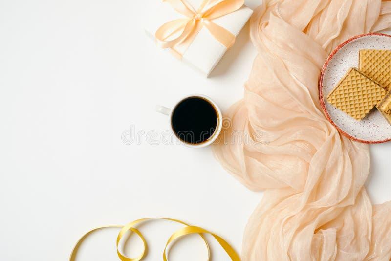 Espacio de trabajo femenino con la bufanda, accesorios de oro, cinta, caja de regalo, taza de café de la mañana en el fondo blanc fotografía de archivo libre de regalías