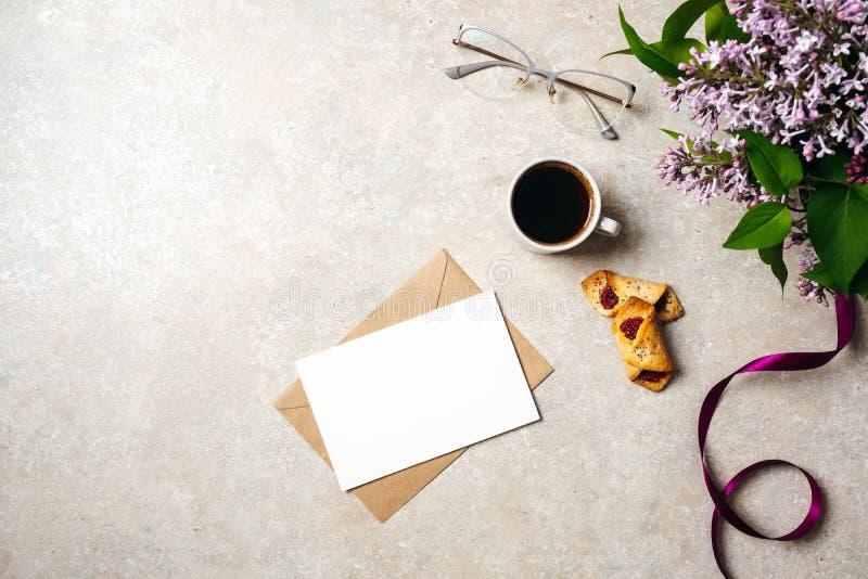 Espacio de trabajo mínimo del escritorio de Ministerio del Interior con la tarjeta de papel en blanco, sobre de Kraft, taza de ca imagen de archivo libre de regalías