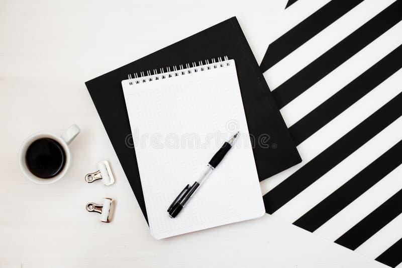 Espacio de trabajo de Minimalistic con el libro, cuaderno, lápiz, taza de café en fondo blanco y negro rayado Opinión superior de imagen de archivo libre de regalías