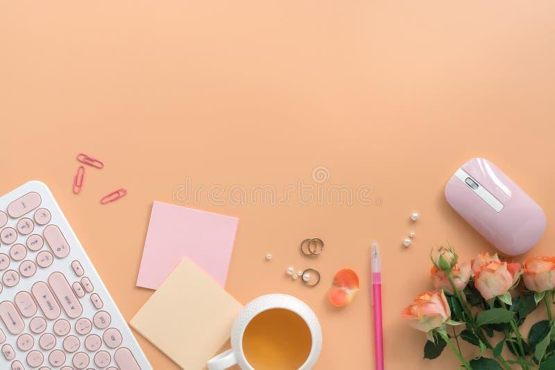 Espacio de trabajo puesto plano de las mujeres - teclado, ratón, taza de té, flores color de rosa, joyería y efectos de escritori imagen de archivo libre de regalías