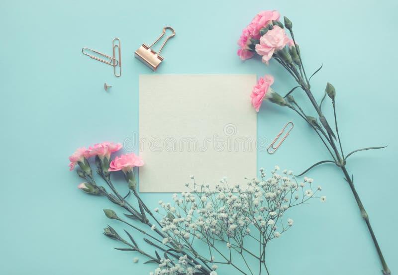 Espacio del Libro Blanco con la flor en fondo del color en colores pastel imagenes de archivo