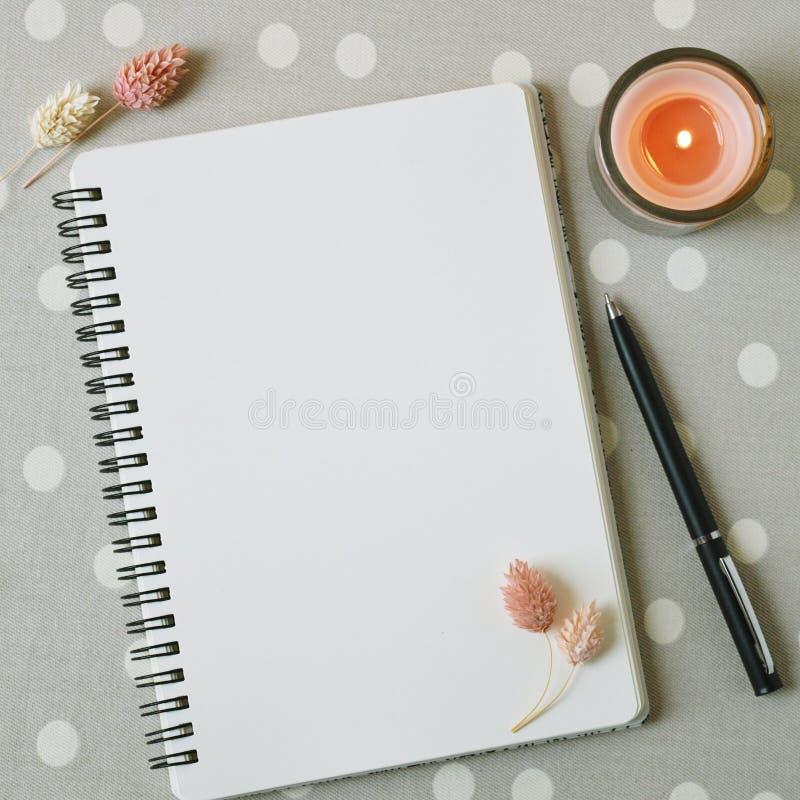 Espacio en blanco de la p?gina blanca del cuaderno, de flores rosadas secadas y de la vela coralina imagen de archivo