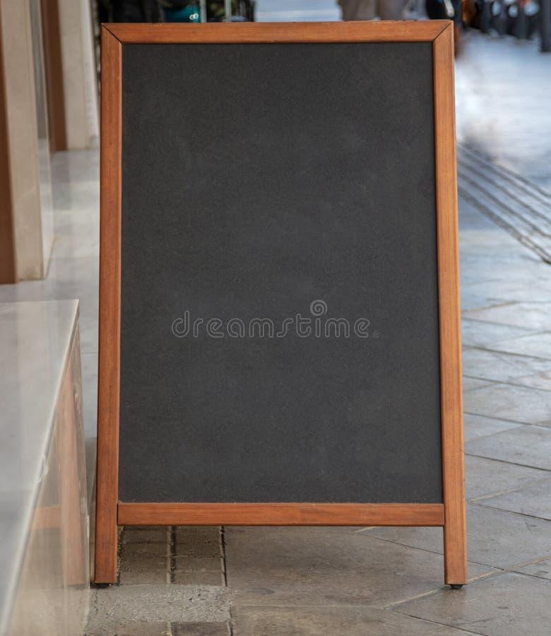 Espacio en blanco de la pizarra con el marco de madera al aire libre en una acera fotografía de archivo