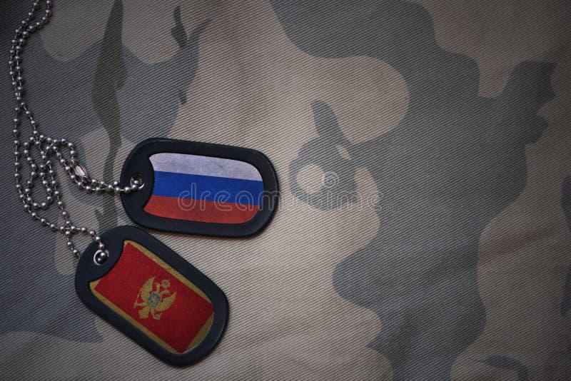 espacio en blanco del ejército, placa de identificación con la bandera de Rusia y Montenegro en el fondo de color caqui de la tex fotografía de archivo libre de regalías