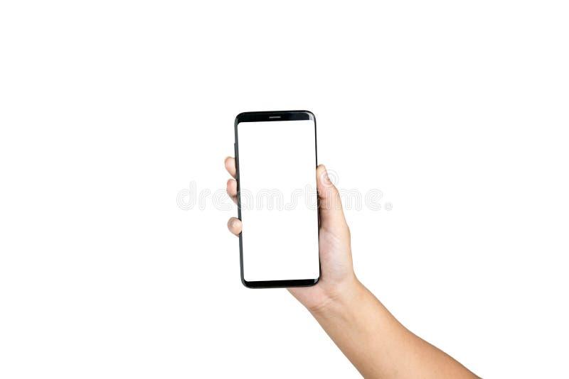 Espacio en blanco del teléfono celular de la demostración de la tenencia de la mano en la pantalla blanca fotografía de archivo
