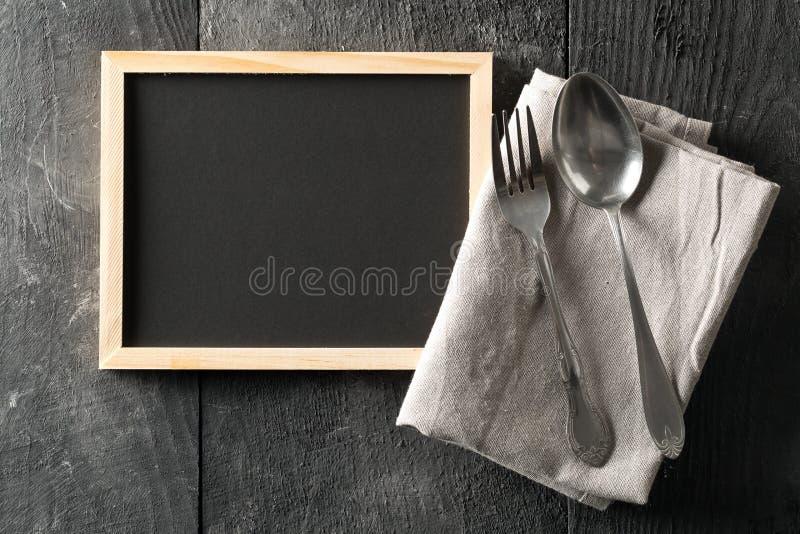 Espacio en blanco, pizarra vacía, negra con la cuchara y los cubiertos de la bifurcación y plano gris de la toalla de plato puest imagen de archivo libre de regalías