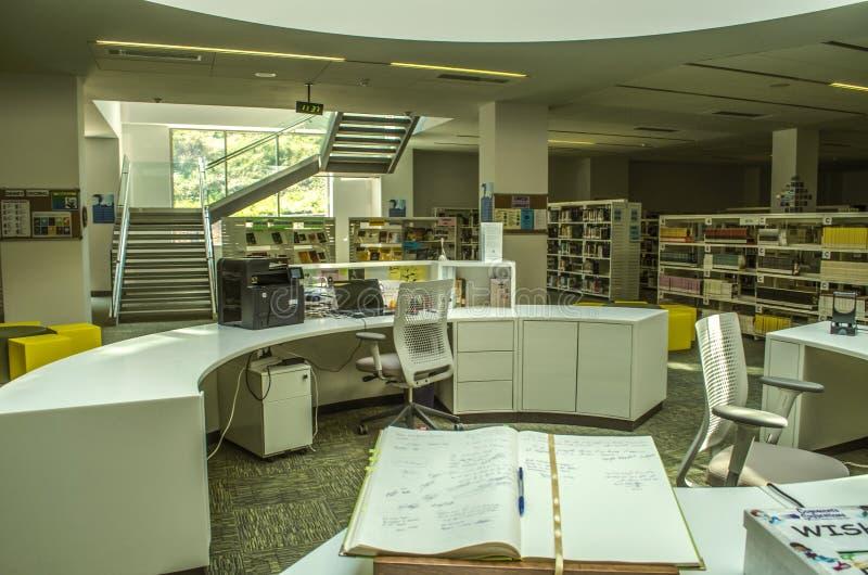 Espacio entre los tramos de escalones, reservados para la biblioteca con los estantes para libros, tabla oval para el deber en el foto de archivo libre de regalías