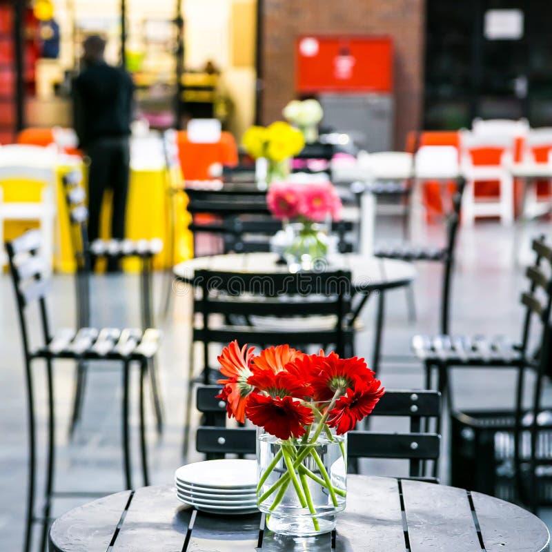 Espacio interior de la cafetería de la cafetería con las flores anaranjadas fotos de archivo libres de regalías