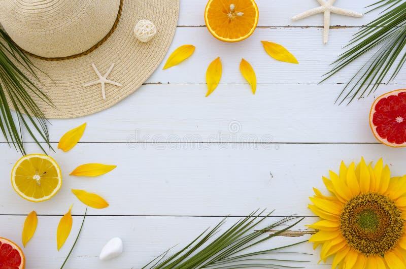 Espacio para poner letras surronded por el marco hermoso con un sombrero del verano, hojas de palma, agrios frescos, girasoles de fotografía de archivo