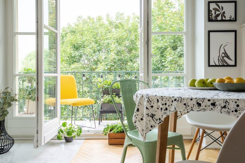 Espacio relajante en un balcón con una silla amarilla vibrante y plantas e hierbas de cosecha propia fuera de un comedor escandin imágenes de archivo libres de regalías