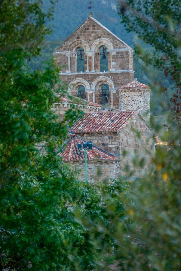 Espadaña de l'église collégiale de San Salvador de Cantamuda parmi les arbres Palencia photographie stock libre de droits