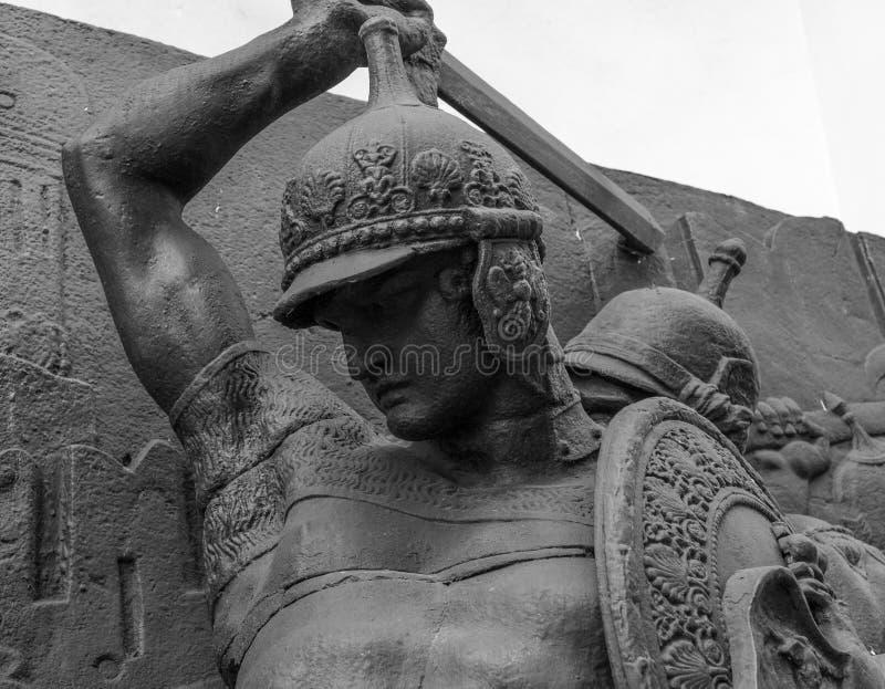Espada à disposição do guerreiro na armadura da estátua medieval do cavaleiro foto de stock royalty free