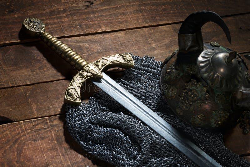 Espada antiga, armadura chain e o capacete do soldado com chifres fotos de stock