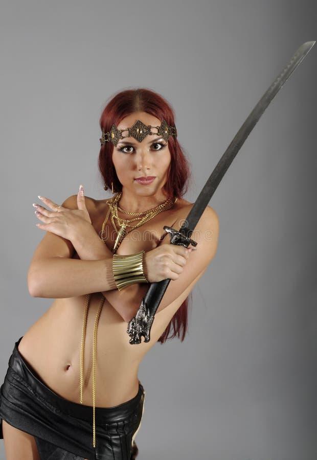 Espada da terra arrendada da mulher do guerreiro em sua mão foto de stock royalty free