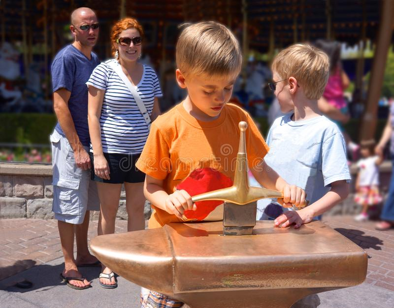 Espada de la familia de Disneyland en la piedra fotos de archivo