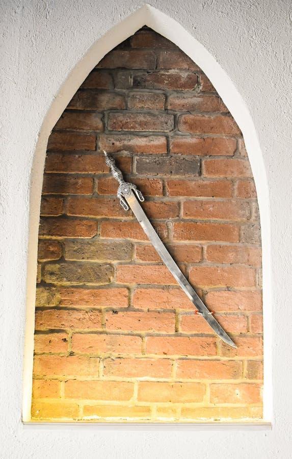 Espada de a?o medieval contra o fundo da parede de tijolo Espada de brilho antiga usada como a decora??o imagens de stock