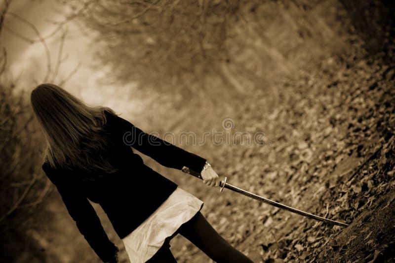 Espada do katana da terra arrendada da mulher nova fotografia de stock royalty free